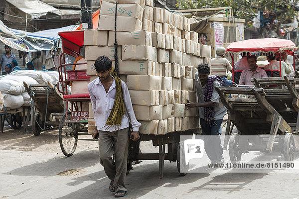 Men transporting goods on a hand cart on Khari Baoli Road