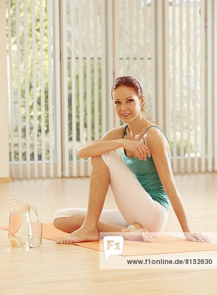 Junge Frau sitzt auf Gymnastik-Matte  daneben ein Krug frisches Wasser