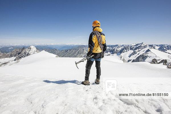 Bergsteiger steht am Gipfel des Schwarzenstein und blickt Richtung Südtirol