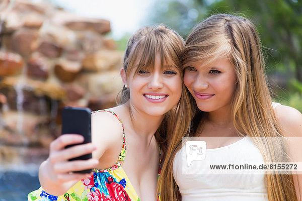 Junge Frauen fotografieren mit dem Smartphone am Swimmingpool  lächelnd