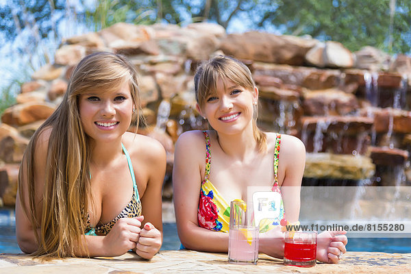 Portrait of young women sitting at swimming pool  smiling
