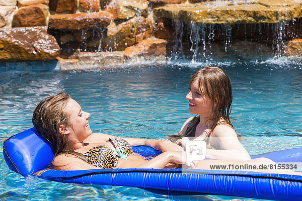 Young women relaxing on float in swimming pool  smiling