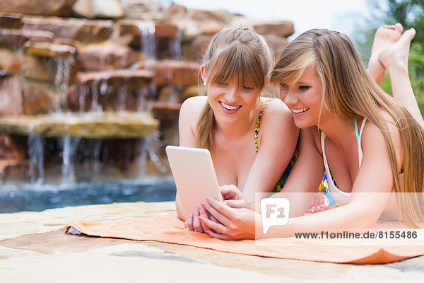 Young women using digital tablet at swimming pool  smiling