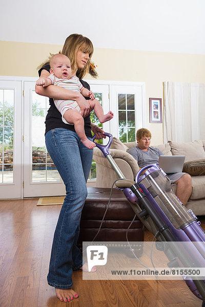 Mutter mit Sohn mit Staubsauger und Vater im Hintergrund