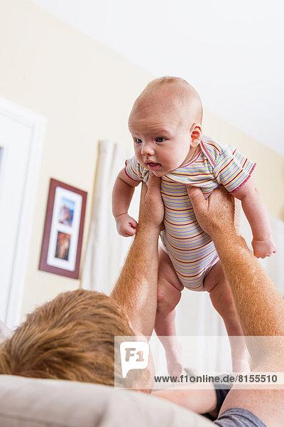 Vater hält seinen kleinen Jungen hoch.