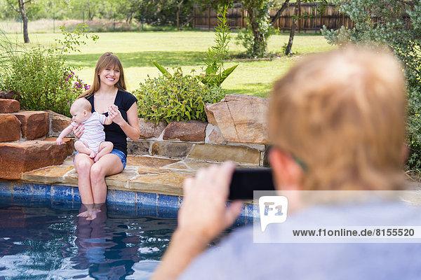 Vater fotografiert Mutter und Kind  lächelnd