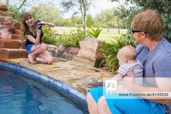 Mutter fotografiert Vater und Kind  lächelnd