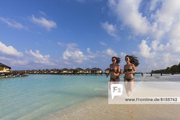 Malediven  Junge Frau und Teenagermädchen laufen am Strand