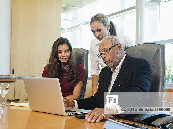 Geschäftsleute arbeiten auf Laptop