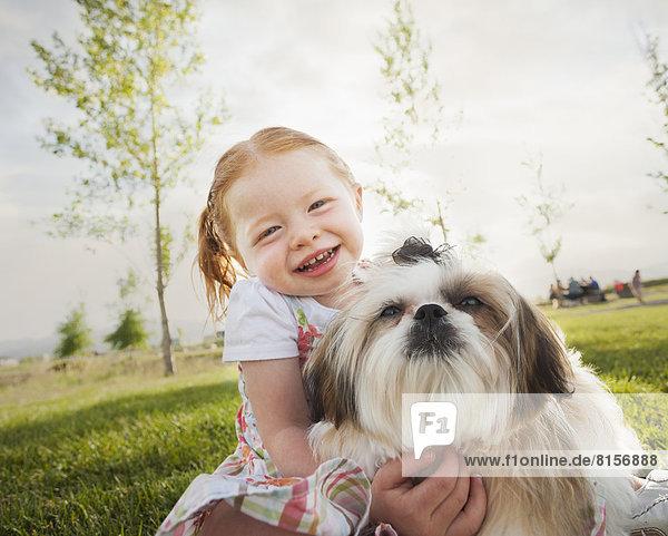 Caucasian girl hugging dog in grass