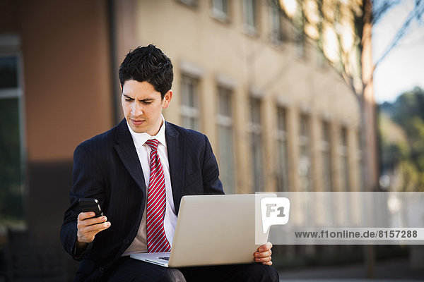 Hispanic businessman using laptop and cell phone