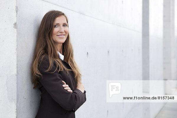 Porträt einer Geschäftsfrau  die sich an die Wand lehnt  lächelnd