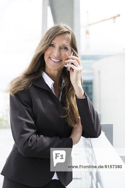 Porträt einer Geschäftsfrau  die auf dem Smartphone spricht  lächelnd