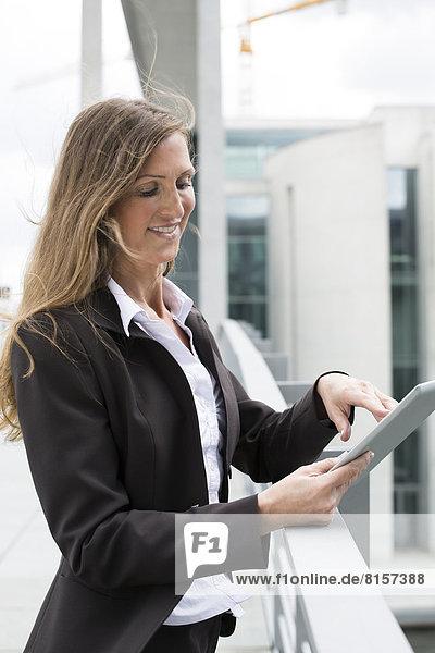 Businesswoman using digital tablet  smiling
