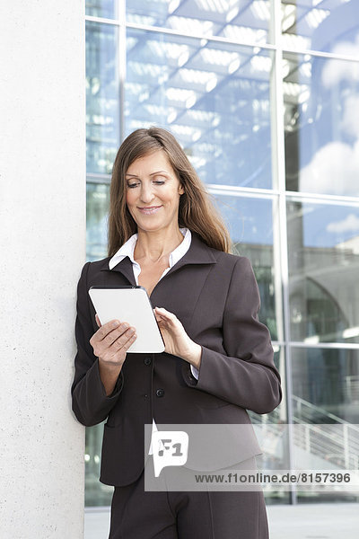 Businesswoman using digital tablet  smiling