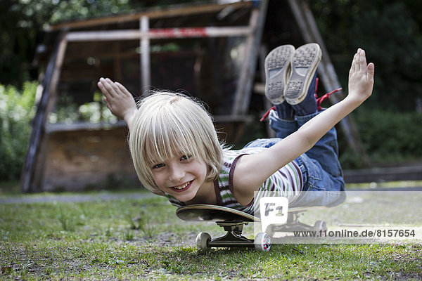 Deutschland  Nordrhein-Westfalen  Köln  Portrait des Jungen auf Skateboard liegend  lächelnd