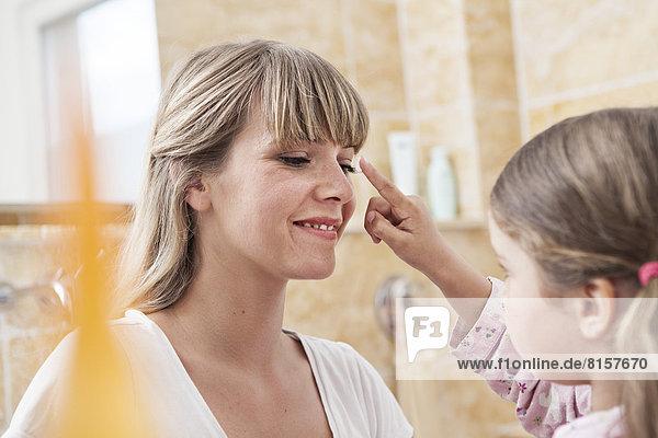 Germany  North Rhine Westphalia    Daughter applying cream to mother in bathroom  smiling