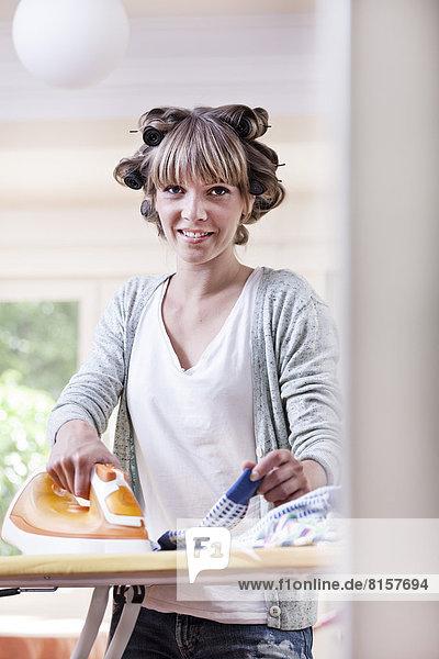 Deutschland  Nordrhein-Westfalen    Porträt einer jungen Frau  die Bügeltücher bügelt  lächelnd