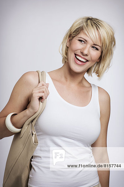 Junge Frau hält Handtasche  lächelnd  Nahaufnahme