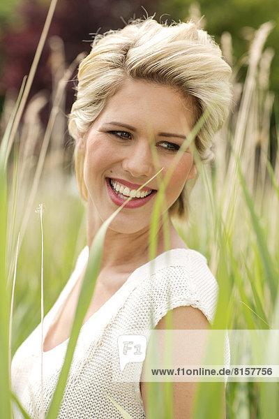 Deutschland  Nordrhein-Westfalen  Junge Frau schaut weg  lächelt  Nahaufnahme