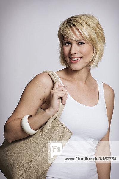 Porträt einer jungen Frau mit Handtasche  lächelnd  Nahaufnahme