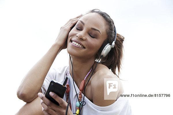 Deutschland  Junge Frau hört Musik mit Kopfhörern  lächelt