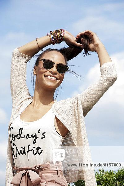 Deutschland  Junge Frau mit Sonnenbrille  lächelnd