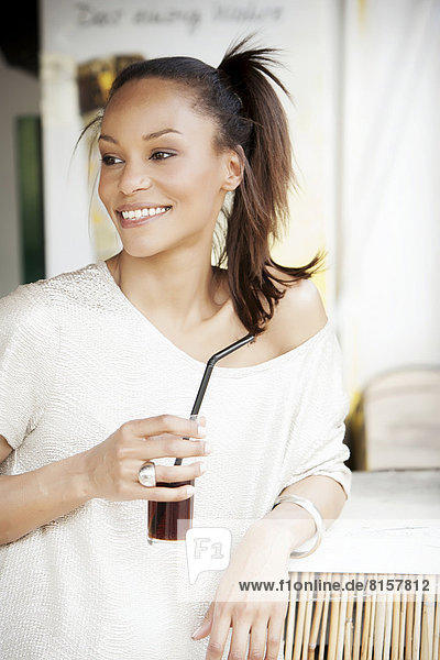 Germany  Young woman holding glass of coke  smiling