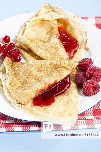 Pancakes with raspberry-jam  raspberries and fresh lowbush cranberries in plate