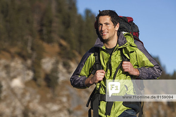 Germany  Mid adult man walking in alps  smiling