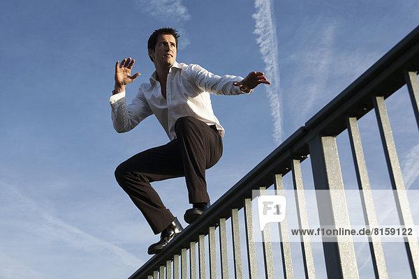 Mittlerer erwachsener Mann auf dem Geländer stehend  wegschauend
