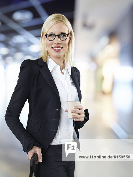 Geschäftsfrau hält Einwegbecher und Aktentasche am Flughafen  lächelnd  Mund