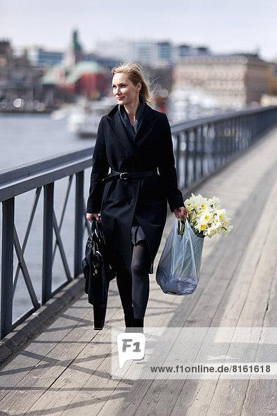 Woman walking with daffodils in shopping bag