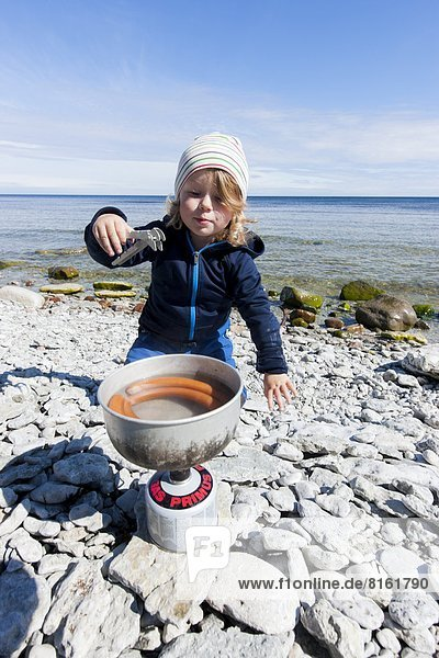 Boy cooking sausages on beach