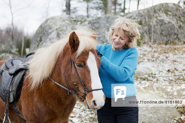 Senior woman with Icelandic horse