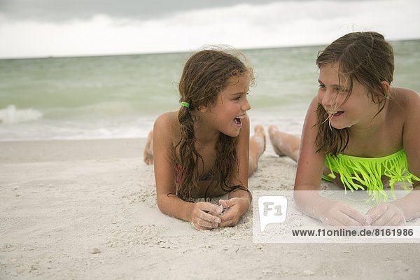 Two girl lying on beach