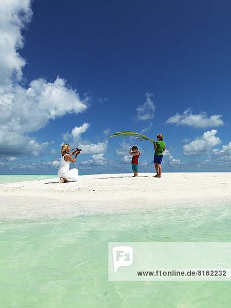 Boys playing on sandy beach while mother taking photo