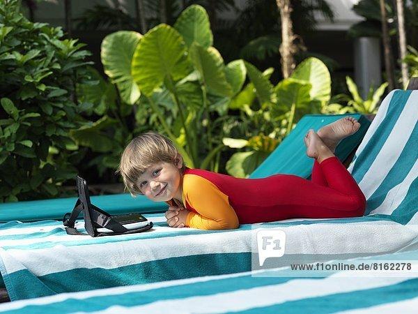Smiling boy lying on sunchair