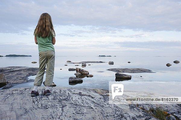 Girl looking at sea  rear view