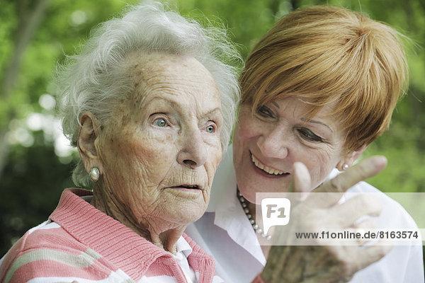 Deutschland  Nordrhein-Westfalen  Köln  Seniorin und reife Frau im Park  lächelnd