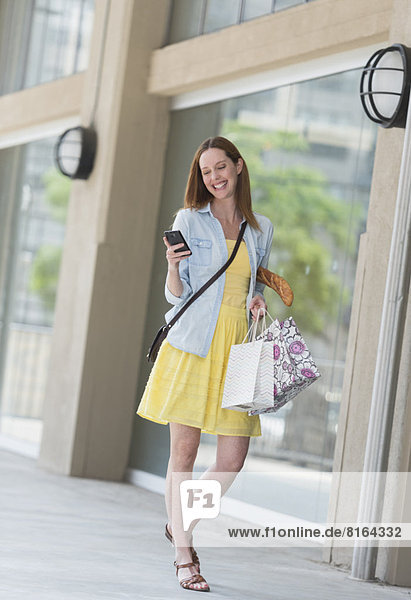 Woman with shopping bags using phone