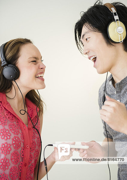 Portrait of young woman and man listening to music on MP3 player