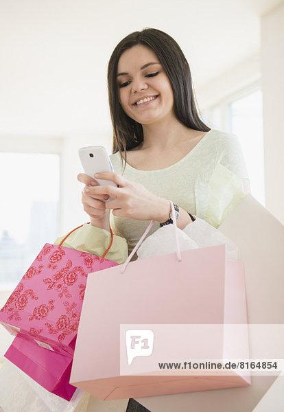 benutzen  Frau  Tasche  Telefon  halten  kaufen  jung  Handy