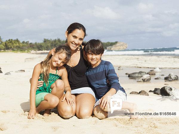sitzend  Portrait  Strand  Junge - Person  5-9 Jahre  5 bis 9 Jahre  10-11 Jahre  10 bis 11 Jahre  Mädchen  Mutter - Mensch