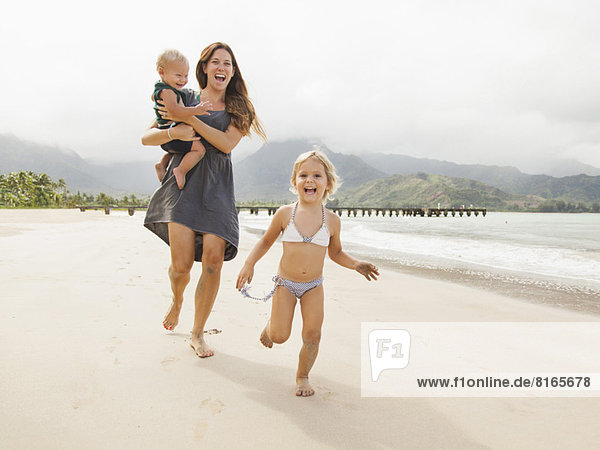 Mother with daughters (6-11 months  2-3) on beach