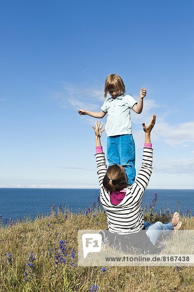 Mother playing with daughter by sea
