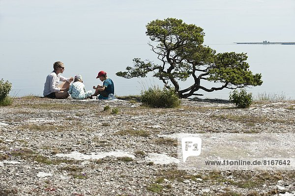 Family relaxing on top of cliff