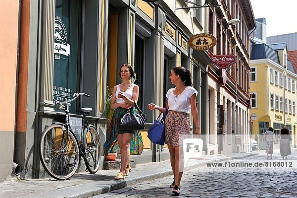 two young girls walking in a street of the Old Town of Riga  Latvia  Baltic region  Northern Europe