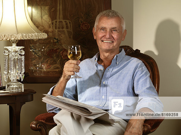 Elderly man sitting in a chair with a newspaper and a glass of wine in his hand
