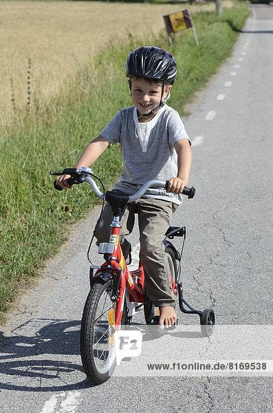 Junge fährt ein Fahrrad mit Stützrädern